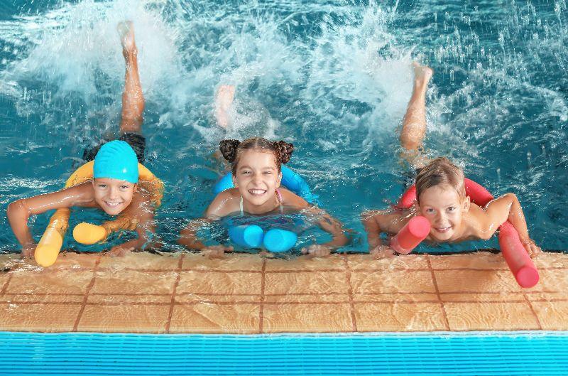 Twee jongens en een meisje drijven met zwemnoodles.