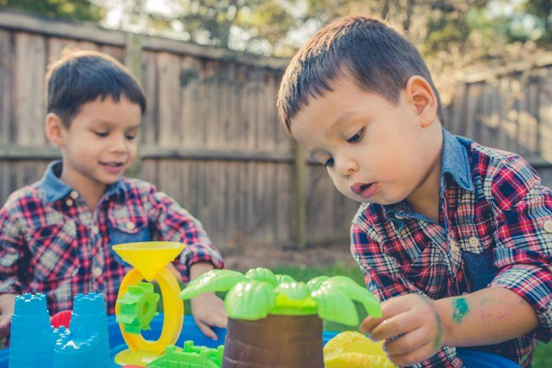 Twee jongens spelen met plastic waterbaan met kasteel en palmboom.