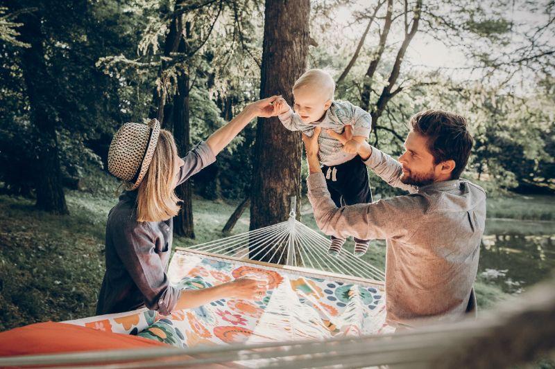 Vrouw en man tillen kind in de lucht boven hangmat