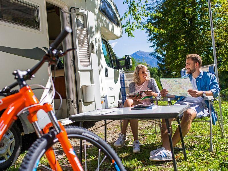 Twee mensen zitten voor camper met tafel en mountainbike