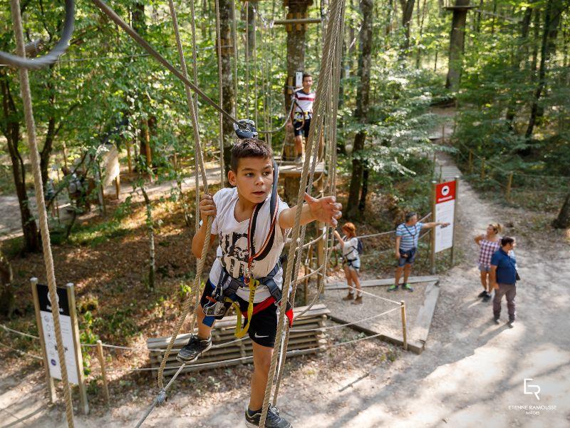 Jongen klimt in touwen in klimpark Acro Givry