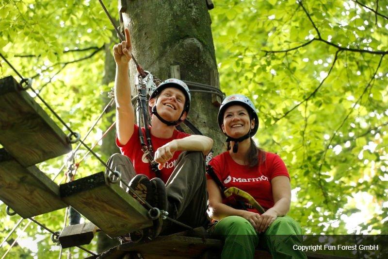 Man en vrouw zitten in een boom in een klimpark